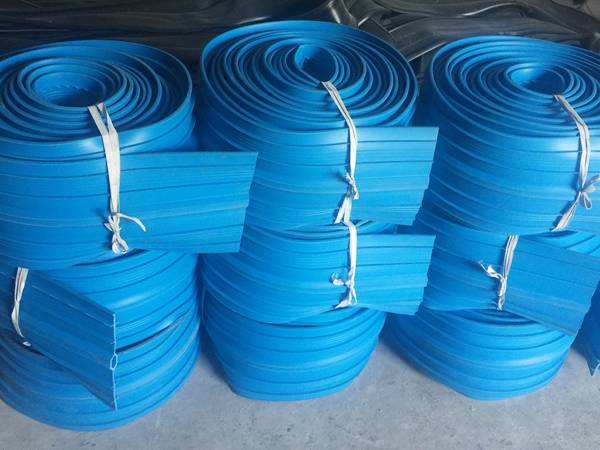 Several coils of bue PVC waterstops on the ground.