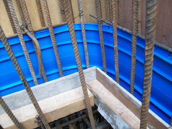 A line of blue PVC waterstops are installed surrounding the building foundation.