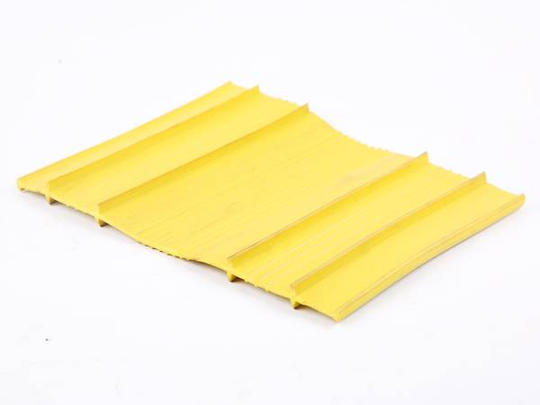 A piece of yellow PVC waterstop without center bulb on gray background.
